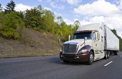 Two tones big rig semi truck transporting cargo in refrigerated semi trailer running on the road with hill on the side stock image