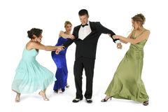Two Too Many. Three beautiful young woman in formal dresses fighting over handsome man in tuxedo. Shot in studio over white Stock Images