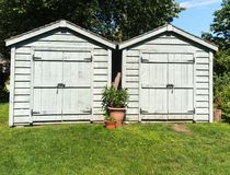 Two Tool sheds. Two Wooden garden sheds with lawn Stock Image