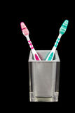 Two tooth brushes in a semi transparent container. Isolated on black background Royalty Free Stock Images
