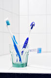 Two toothbrushes. Two blue toothbrushes in a glass on edge of bathtub stock images