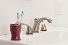 Two Toothbrushes. Concept with two toothbrushes in a bathroom, one green and one pink, commitment step Stock Images