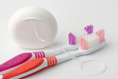 Two toothbrushes and dental floss stock images