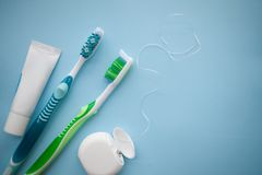 Two toothbrushes and dental floss on blue background Stock Photos
