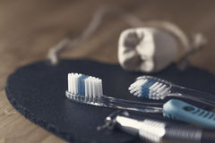 Two toothbrushes with a dentists drill. And mold of tooth lying on a black mat with focus to the bristles of one brush in a dental and healthcare concept Stock Image