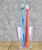 Two toothbrushes in a transparent plastic cup in the bathroom on a concrete background. royalty free stock photography