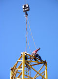 Two on Top. Construction workers kneeling on a scaffold high above the ground setting the hooks from a crane Stock Photography
