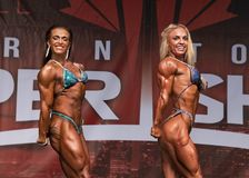 Muscle Babes Pose Down at 2018 Toronto Pro Supershow. Two top contenders at the Women`s Pro Physique contest of the 2018 Toronto Pro Supershow compare triceps stock image