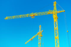 Two tops of construction cranes on sky Royalty Free Stock Images