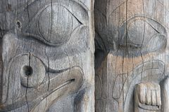 Two Totems. Detail of two faces on a pair of old, worn, unpainted, wooden West Coast Indian totem poles in a Vancouver, British Columbia park Stock Images