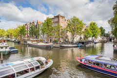 Two tourboats at a canal intersection in Amsterdam Stock Photos