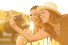 Two tourist friends taking selfies in hotel balcony Stock Images