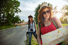 Two Tourist Girl Hitchhiking Stock Image