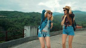 Two tourist girlfrends enjoying the rain in the mountains stock footage