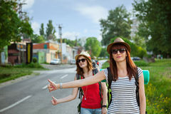 Two Tourist Girls Hitchhiking Stock Photo
