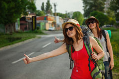 Two Tourist Girls Hitchhiking Stock Photography