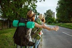 Two Tourist Girls Hitchhiking Stock Image