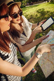 Two Tourist Girls Using Map And Digital Tablet Stock Photography