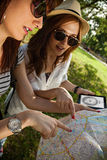 Two Tourist Girls Using Map And Digital Tablet Royalty Free Stock Photography