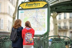 Two tourist looking at the map of Parisian metro Stock Photos