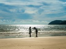 Two Tourist Taking Photo in the Beach. With Blue sky and waves. Located in Cenang Beach Langkawi Malaysia royalty free stock photo