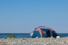 Two tourist tents on a pebble sea shore in the morning royalty free stock photography