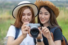 Two tourist woman taking a photo with camera in nature stock image
