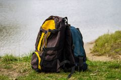 Two touristic backpacks on the riverbank. Hike concept Royalty Free Stock Image