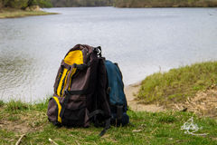Two touristic backpacks on the riverbank Stock Image