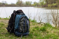 Two touristic backpacks on the riverbank. Hike concept Stock Photos
