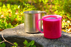 Two Touristic Cups metal and pink plastic with Tea on stone Royalty Free Stock Photography