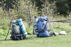 Two touristic hikers backpacks standing in a mountain valley on. Sunny day Royalty Free Stock Image
