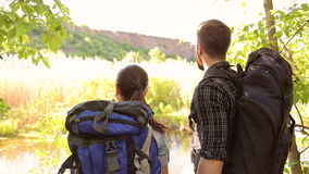 Two tourists with backpacks enjoying view of lake. Couple of tourists with big Hiking backpacks, enjoying the view of the lake and mountains. Close-up stock video