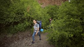 Two tourists with backpacks walk along a trail. Young people,man and woman are traveling with backpacks in the mountains. Two tourists with backpacks walk along stock video