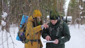 Two tourists with backpacks, a young man and a girl, in a winter snow-covered forest look at a paper map. Slow motion stock video