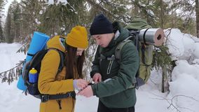 Two tourists with backpacks, a young man and a girl, in a winter snow-covered forest look at a paper map. Slow motion stock video footage
