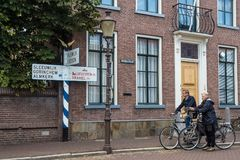 Two tourists on bicycles are pausing in front of an old signpost in Woudrichem, Holland Royalty Free Stock Photography