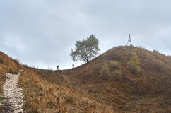 Two tourists climb the path to the top of the mountain. Stock Images