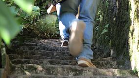 Two tourists climb the stairs. Two tourists climb the stairs, the place is surrounded by lush vegetation (CLOSE UP stock video footage