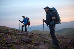 Two tourists at dawn in mountains Royalty Free Stock Images