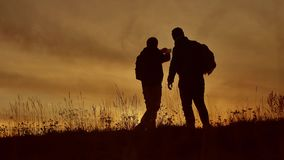 Two tourists do selfie at sunset silhouette of sunlight. Travel two people in jackets do selfie autumn lifestyle. Two tourists do selfie sunset silhouette of stock video footage