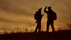 Two tourists do selfie at sunset silhouette of sunlight. Travel two people in jackets do selfie autumn silhouette. Two tourists do selfie at sunset silhouette stock footage