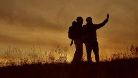 Two tourists do selfie at sunset silhouette of sunlight. Travel two people in jackets do selfie lifestyle autumn. Two tourists do selfie at sunset silhouette of stock video footage