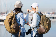 Two tourists harbor. Rear view of two female tourists by the harbor and pointing at distance Stock Images