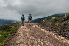 Two tourists hiking along in the mountain road, Turkey royalty free stock photography
