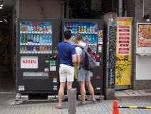 Two tourists at Japanese vending machine. Two tourists in Tokyo Japan try to work out how to order from a Japanese vending machine Stock Photo