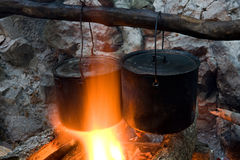 Two Tourists Kettles On Campfire Stock Photography