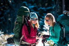 Two tourists look at the phone. Two friends travel together. Women with backpacks in the winter mountains. Winter hike. Walk through the snowy forest. Mobile royalty free stock photos