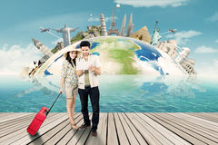 Two tourists look at world map on tablet Stock Image
