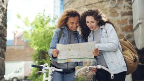 Two tourists are looking at map standing in the street holding bicycles and talking. Attractive young women and casual. Two lost tourists are looking at map stock video footage